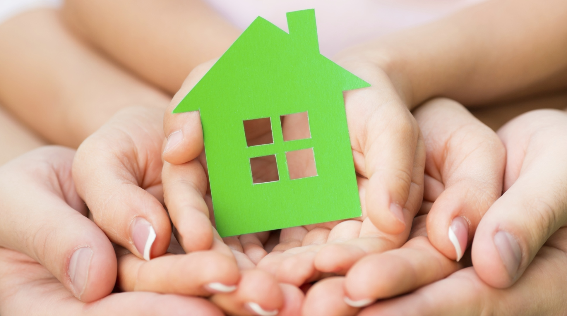 Family holding green paper house